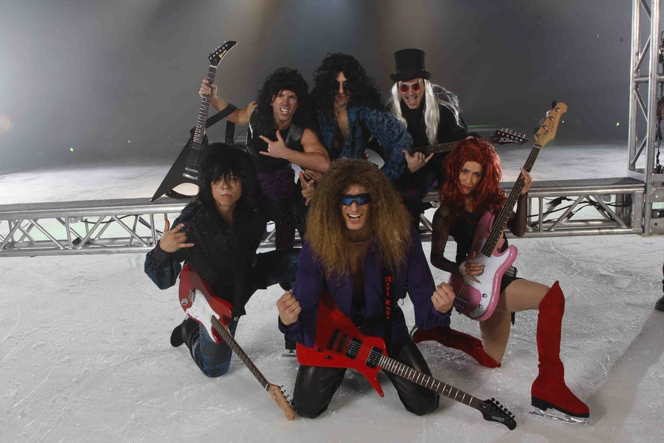 Stars on Ice cast wearing wigs and holding guitars