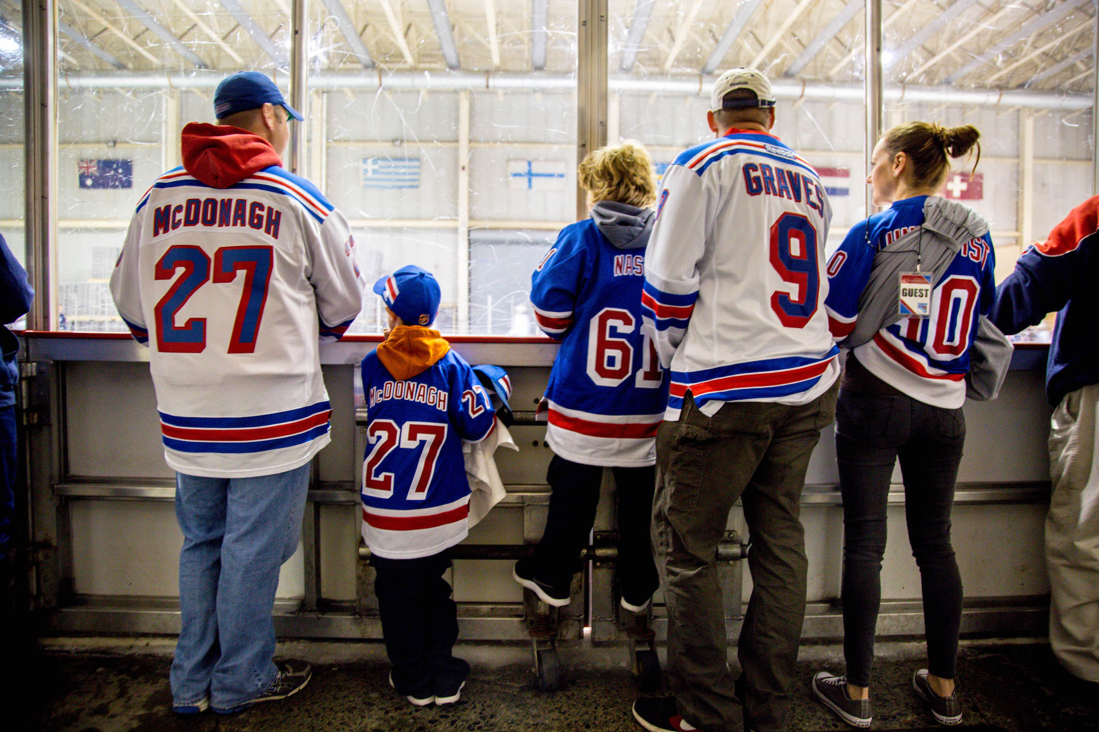 Family in hockey jerseys watching hockey game at rink