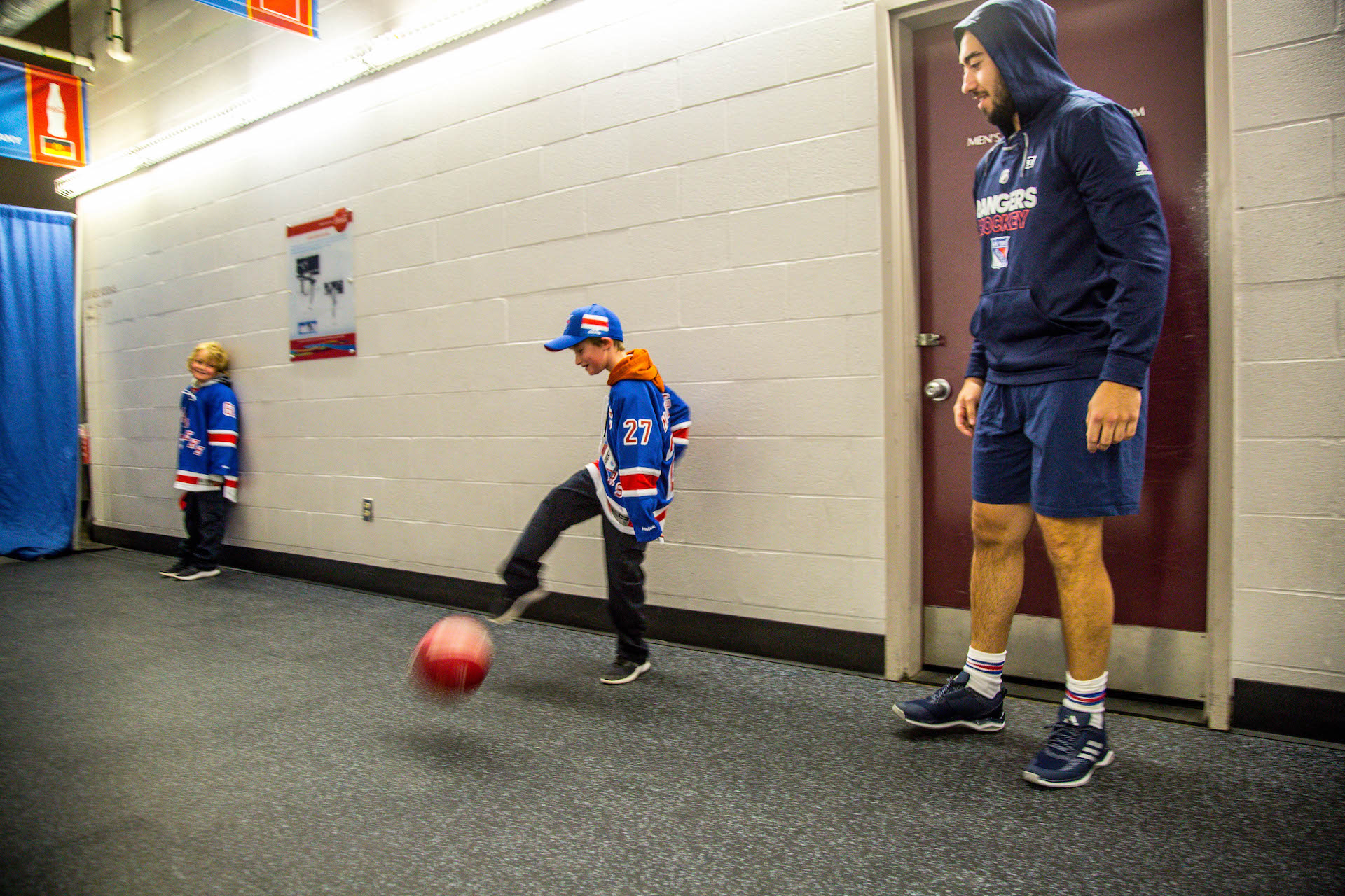 Kid kicking ball with adult at an arena