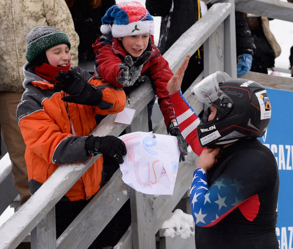 Two boys cheering on Steven Holcomb and holding team USA sign.