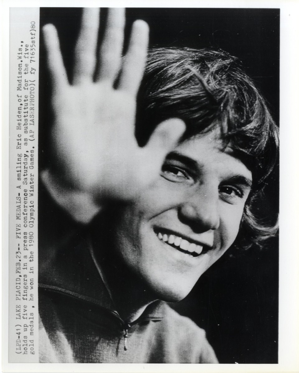A smiling Eric Heiden holding up five fingers in a press conference as a substitute for the five gold medals he won