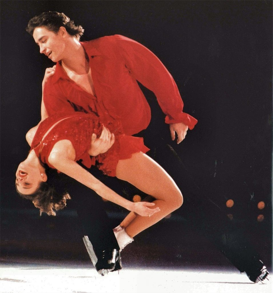 Ekaterina Gordeeva and Sergei Grinkov ice skating in red outfits