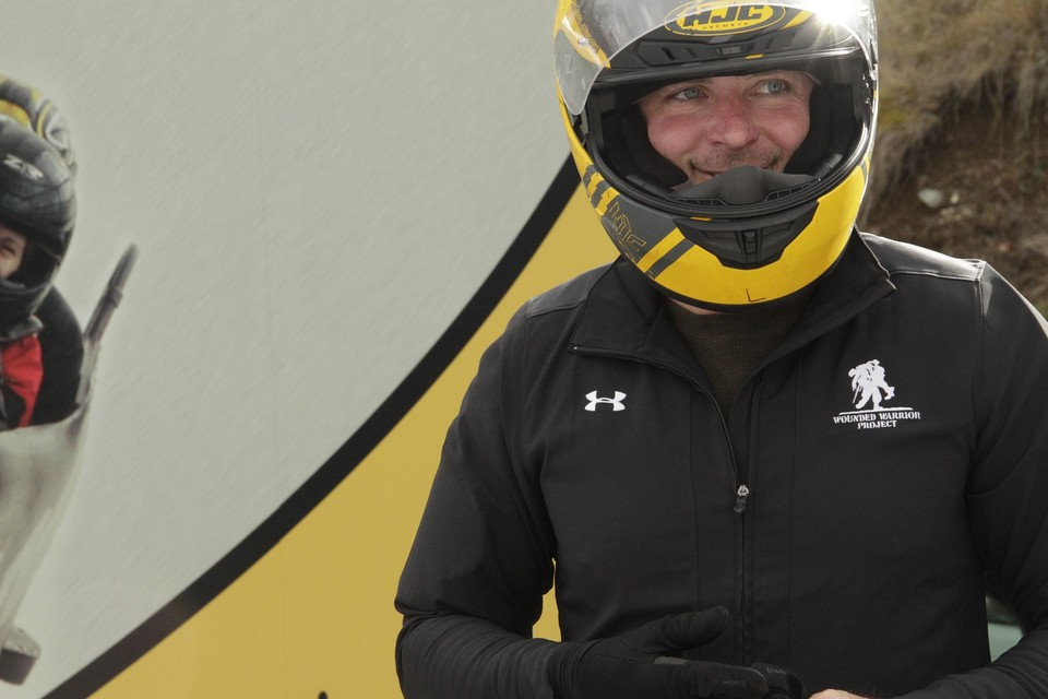 Picture of smiling bobsled athlete in yellow helmet.