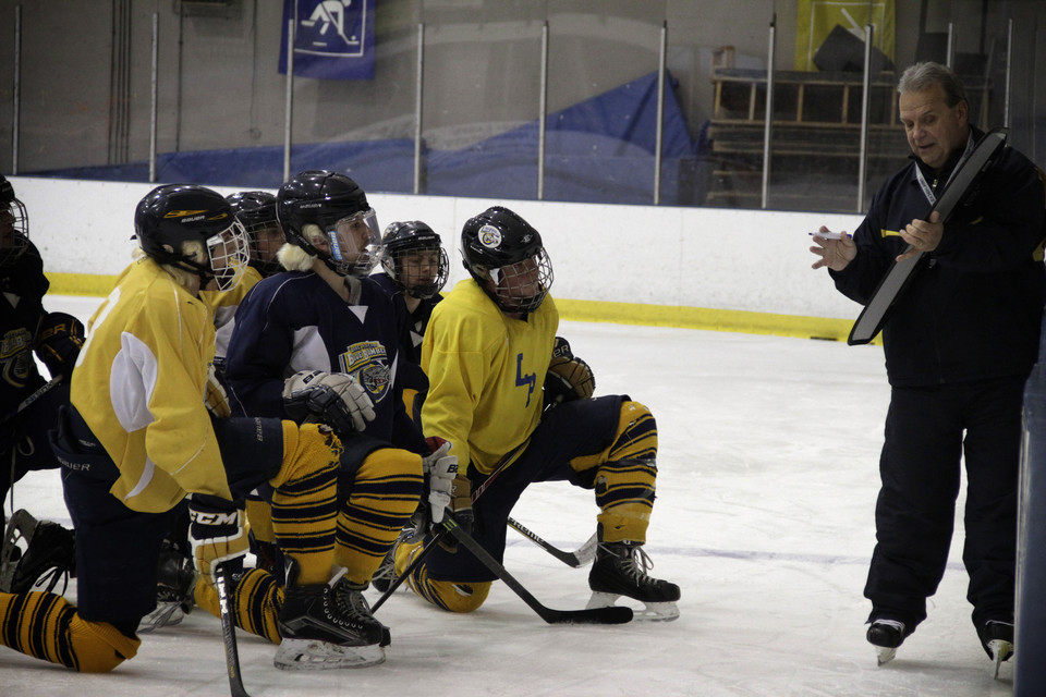 Butch giving instruction at practice on ice rink