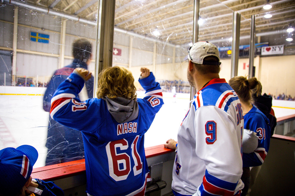 Boy in hockey jersey knocking on glass surrounding ice rink
