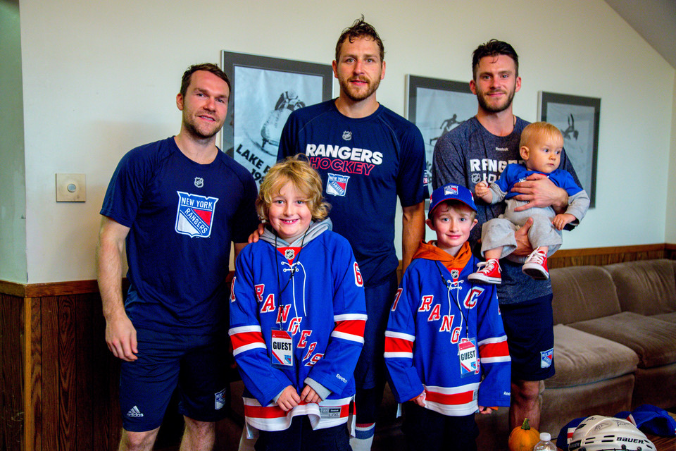 Two young boys and a baby posing with Ranger's hockey players