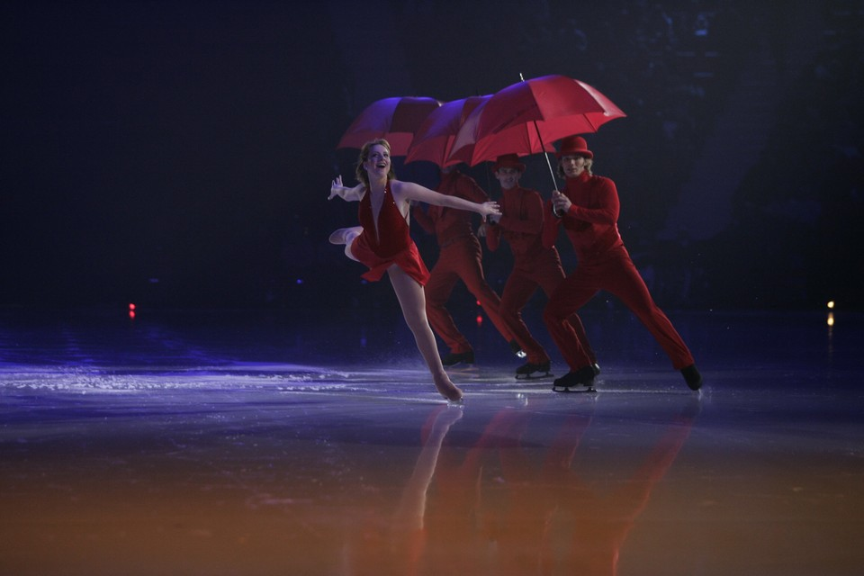 John Zimmerman, David Pelletier, Steven Cousins, Sarah Huges and Todd Aldridge ice skating in red outfits with red umbrellas