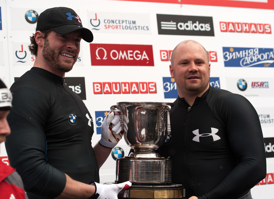 Steven Holcomb (R) and Steven Langton of The United States hold the Houben Trophy after their win